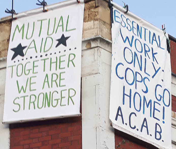 """two hanging banners: """"mutual aid - together we are stronger"""" and """"essential work only: cops go home! A.C.A.B."""""""