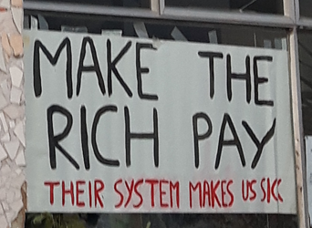 """banner saying """"Make the Rich Pay: Their System Makes Us Sick"""""""