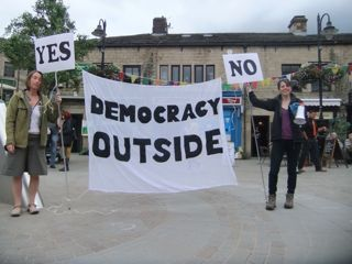 Two performers hold banner and placards in Hebden Bridge