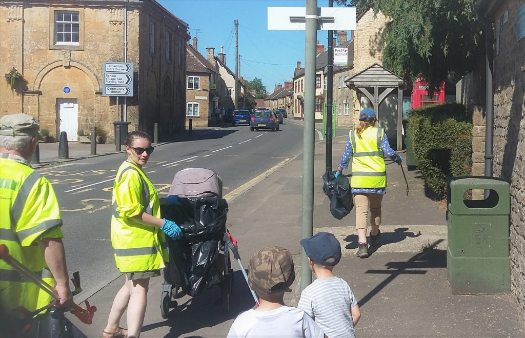 Three adults and two children litter picking on Milborne Port High Street