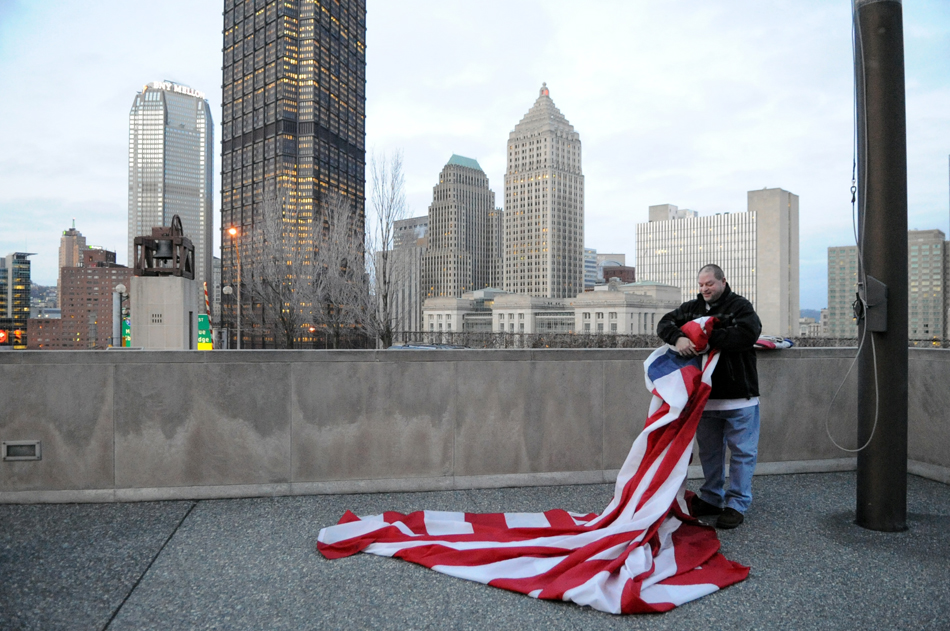 Joel Zwibel, 43, of West View replaces the historic flag with the Bennington Flag at Flag Plaza, Uptown, Monday, February 20, 2012.  There is a different historic flag flown for every day of the month.  (Jasmine Goldband  |  Tribune-Review) (JLG Flag0226.jpg:, goes with Craig Smith story).