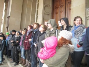 Protesters link arms to block main entrance of council house.