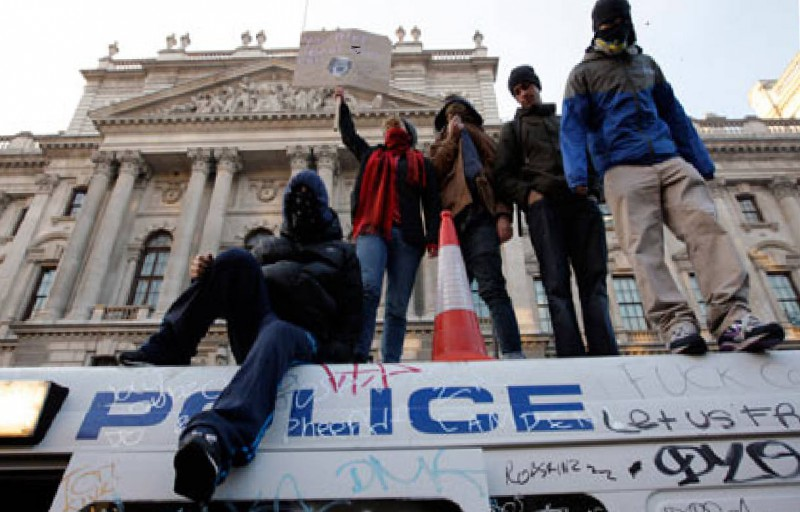 Picture of demonstrators stood on top of a graffiti-ed police van